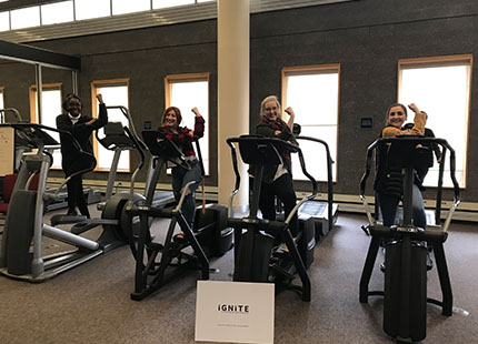 Three members of iGNITE and VP Lorretta Holloway on ellipticals posing like Rosie the Riveter.
