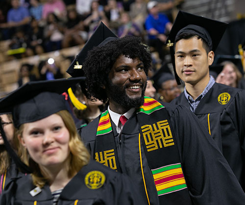 Three students prepare to receive their diplomas at the DCU Center in Worcester during the FSU 2018 Commencement