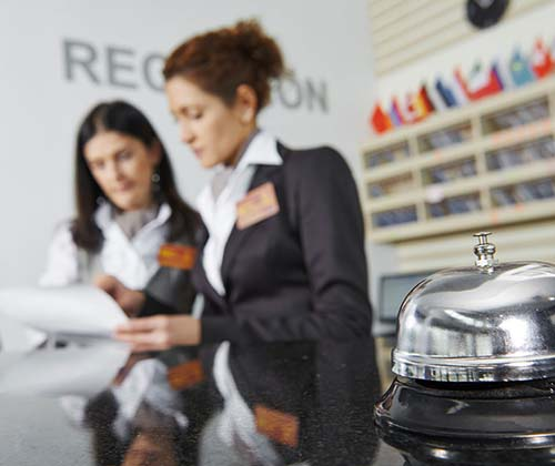 Two women work at a hotel reception desk