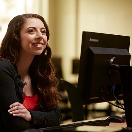 Female business student sitting in class at computer