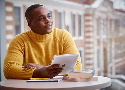 Male student holding an iPad in a study lounge