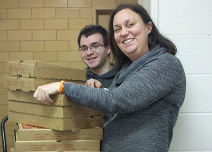 Computer Science student and employer hold stack of pizza boxes