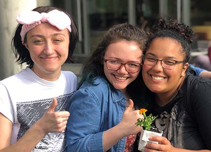 three students holding a flower