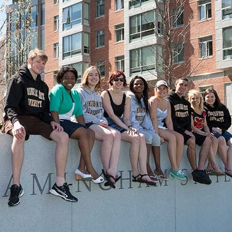 Smiling students sitting on Framingham State University wall on Accepted Students Day