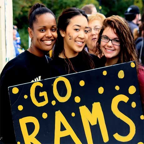 "Students at Homecoming with a sign that reads ""Go Rams"""