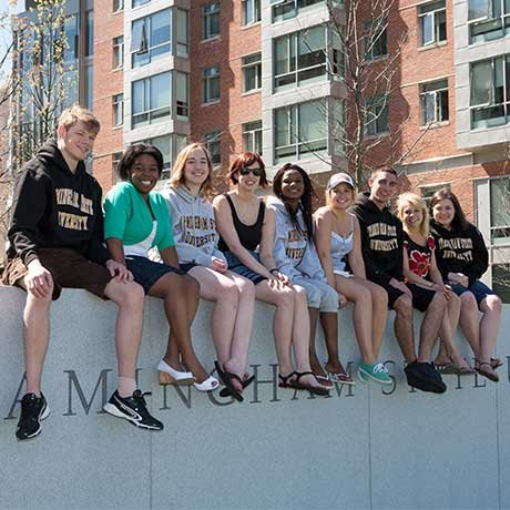 "Group of students sitting on a wall that reads, ""Framingham State University"""